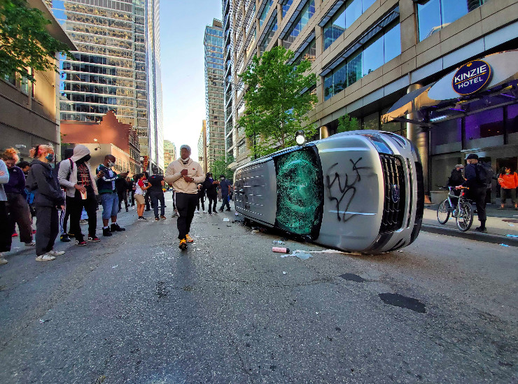 A police SUV is rolled on its side by protesters during clashes with police Saturday near the Kinzie Hotel at 20 W. Kinzie St. in the Loop.