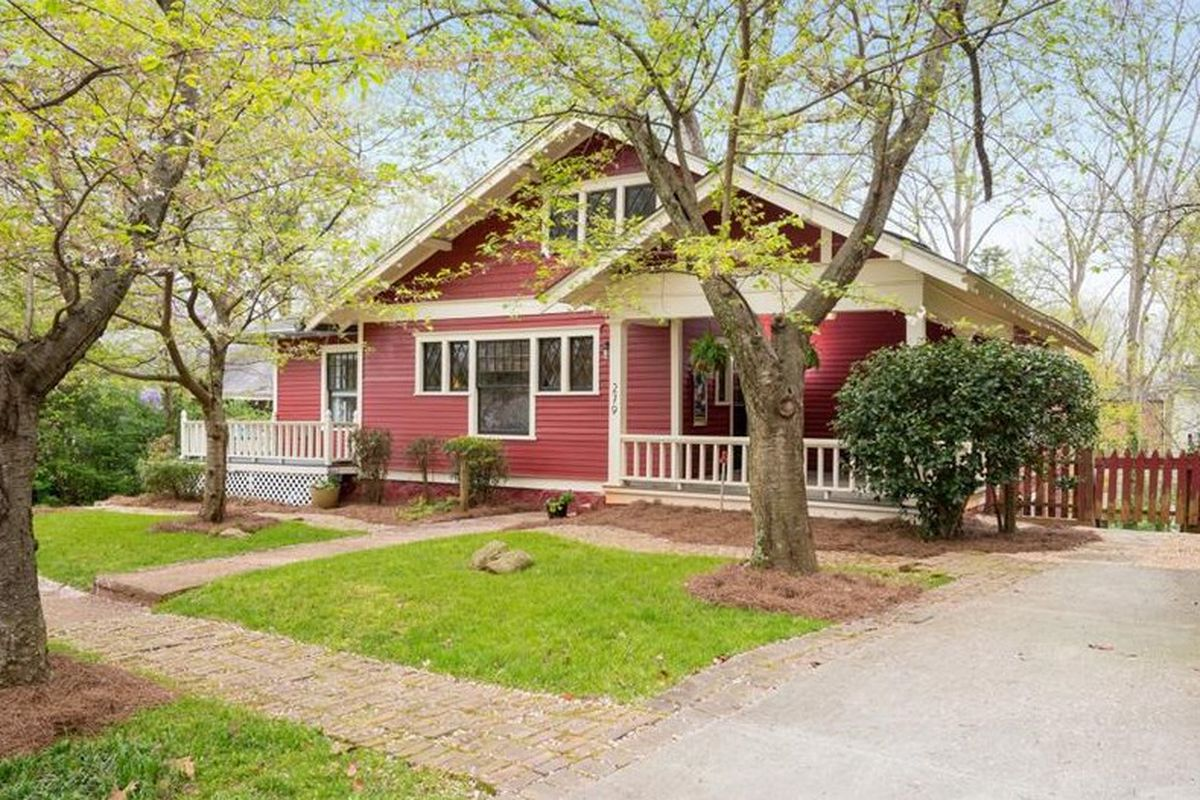 Red house with covered porch and landscaped yard.