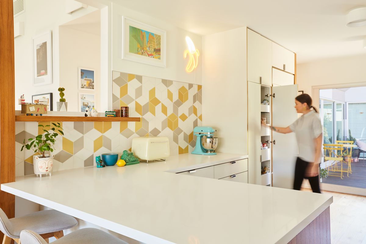 A kitchen with white cabinetry and a backsplash with orange, gray, and white patterned tiles.