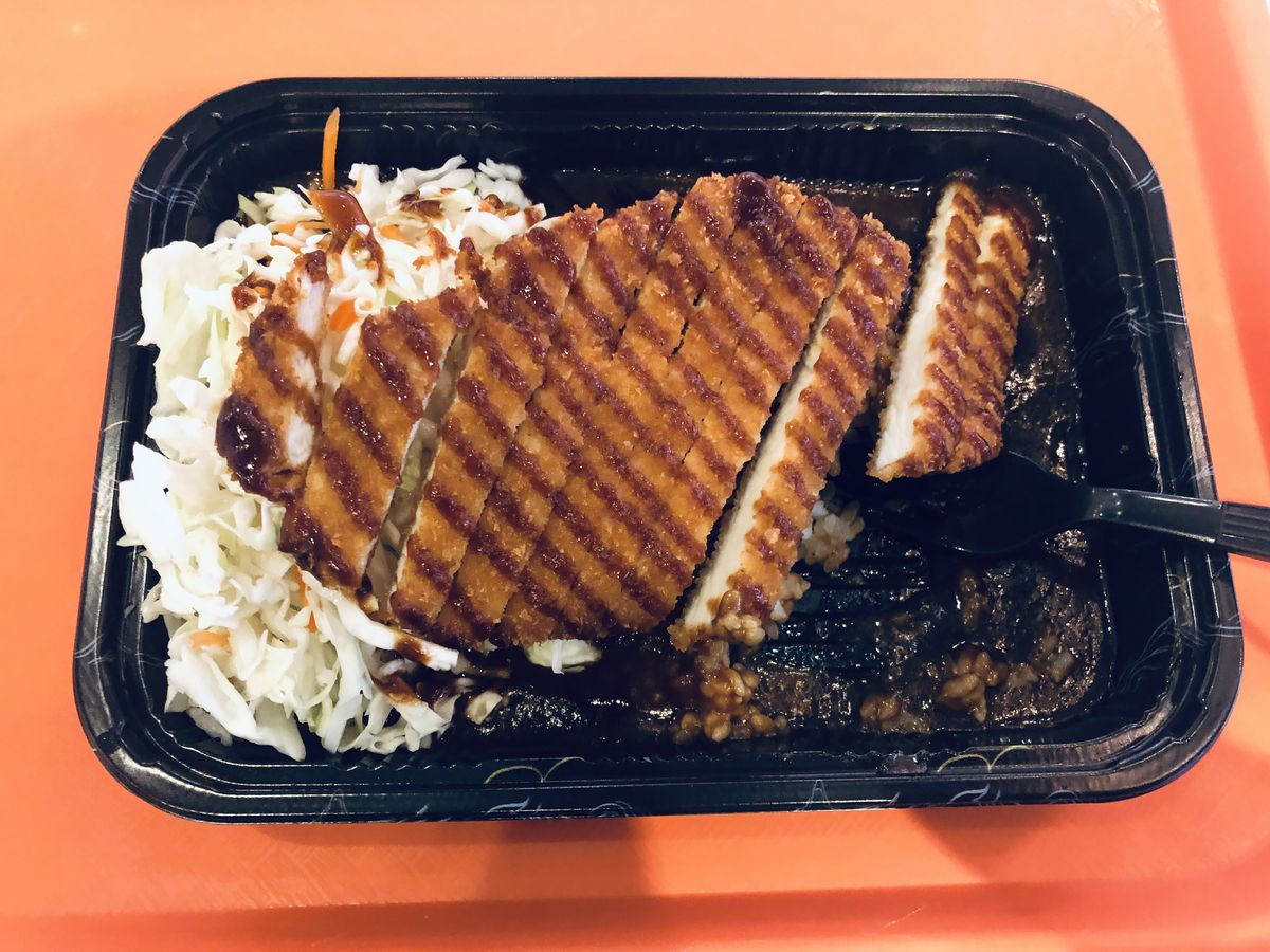 A fried chicken cutlet sits atop a bed of rice and brown curry. The cutlet is drizzled with sweet barbecue sauce. It is plated on a black takeout container, which is situated on top of a bright orange tray.