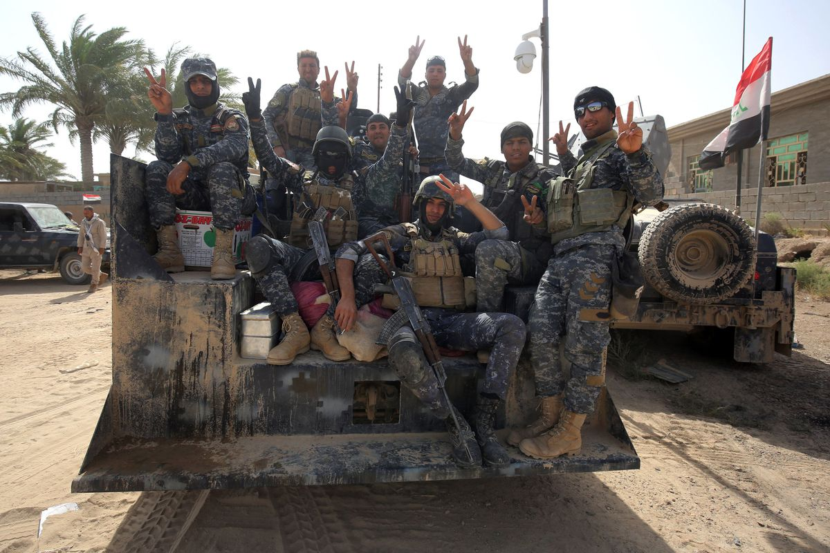 Iraqi government forces pose for a picture in al-Shahabi village, east of Fallujah, on May 24, 2016, as they take part in a major assault to retake the city from ISIS.