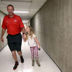 Larry Krystkowiak, head coach for the Utah Runnin' Utes basketball team, walks with his daughter Finley between his sons' basketball games in the Team Camp tournament at the University of Utah in Salt Lake City on Friday, June 12, 2015.