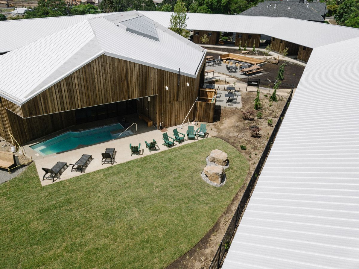 Aerial view of a building clad in wood with a pool under the ceilings. A row of lounge chairs are on the patio.
