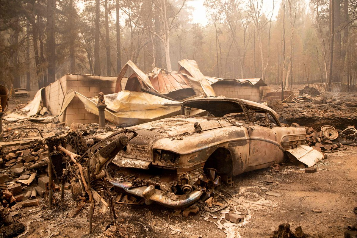 A burned classic car sits among the smoldering remains of a home during the Dixie fire in the Indian Falls neighborhood of unincorporated Plumas County, California on Monday. The Dixie fire has now burned more than 190,000 acres and continues to edge closer to more residential communities.