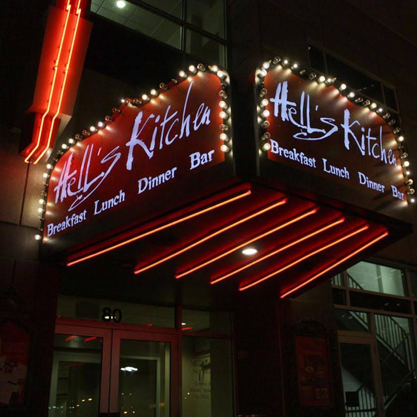 The dark red, white lit sign for the restaurant at night