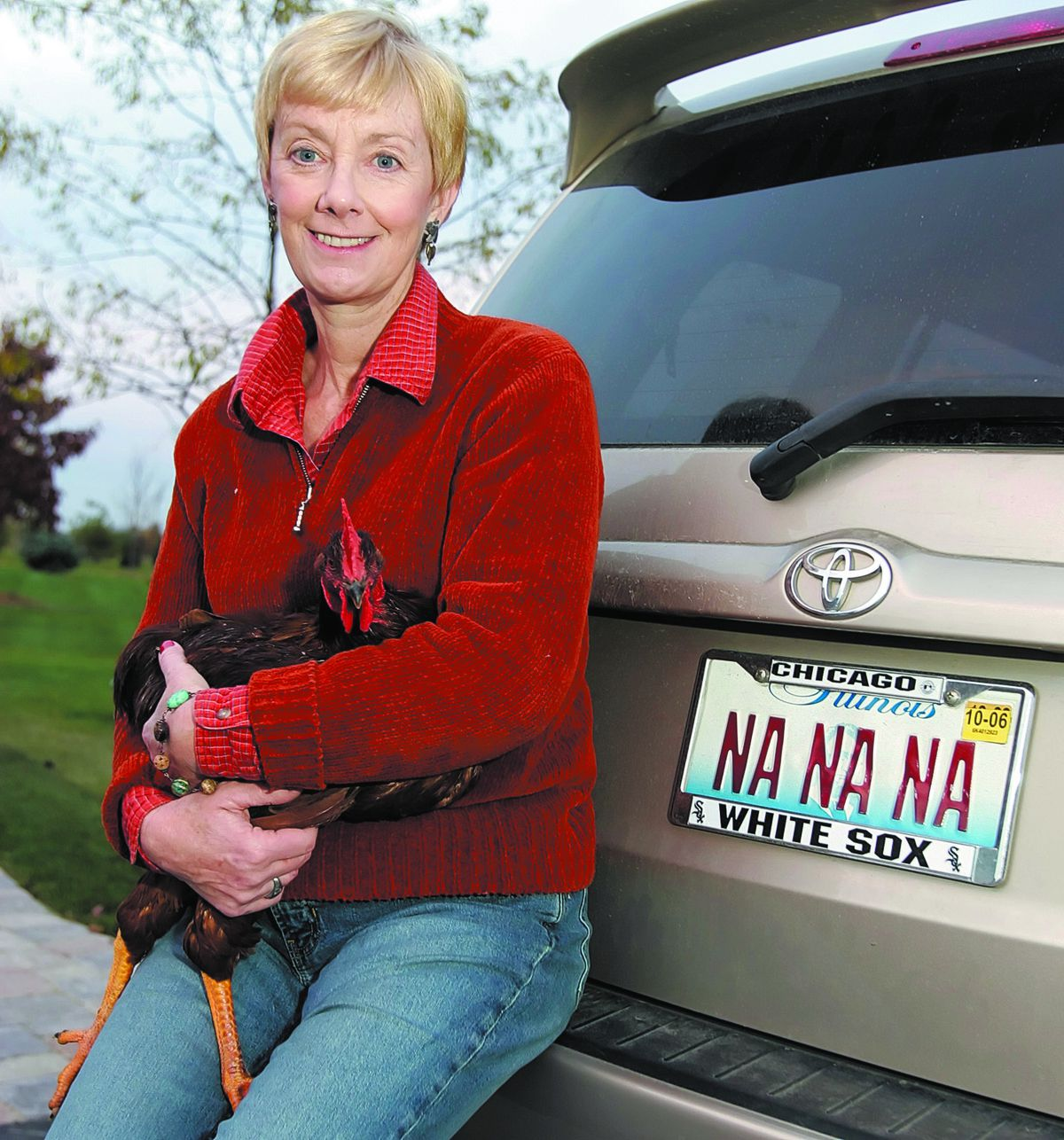 """Famed White Sox organist Nancy Faust, in November 2005, with her rooster named """"Ozzie"""" and her license plate that refers to her signature song """"Na Na Hey Hey Kiss Him Goodbye."""""""
