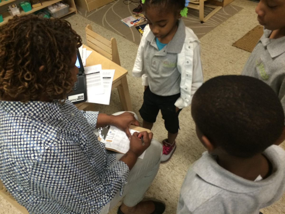 Teacher Marva Bell checks a student's work at Libertas School of Memphis, a charter school run by a Tennessee-based operator in the Achievement School District.