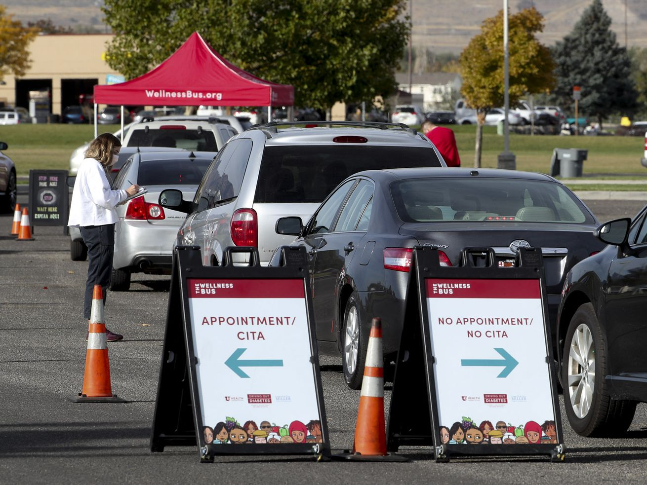 Vehicles form a line for COVID-19 testing as the University Health Wellness Bus visits Centennial Park in West Valley City on Monday, Oct. 19, 2020.