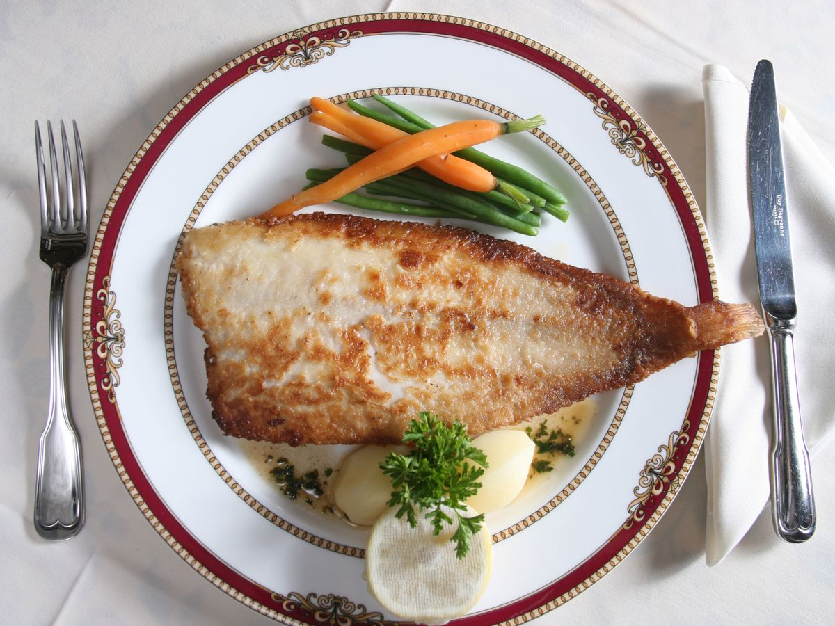 Seared fish with carrots, gree beans, and parsley garnish on a fancy plate