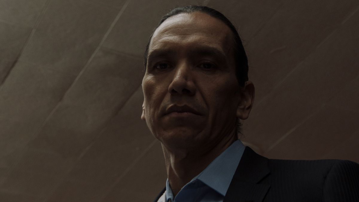 Low angle shot of Michael Greyeyes in a suit looking down in Wild Indian