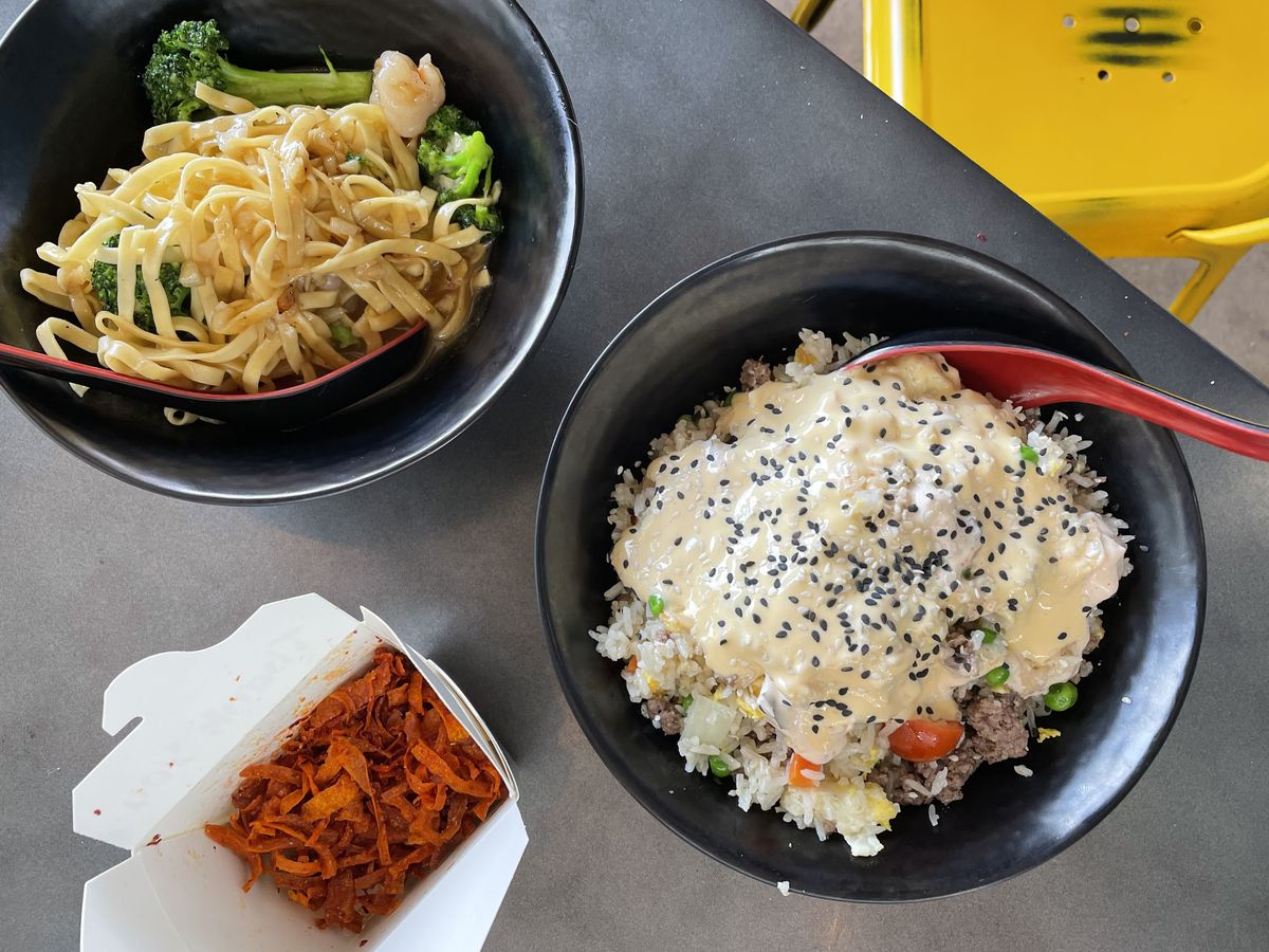 Bowls of garlic noodles with shrimp and broccoli and cheeseburger fried rice with a takeout box of carrot chips