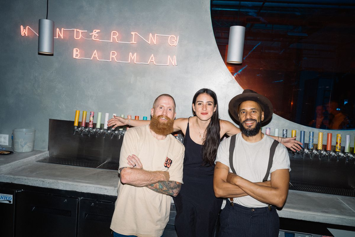 The co-founders of Wandering Barman stand arm-in-arm at a friends and family event ahead of the taproom's opening.