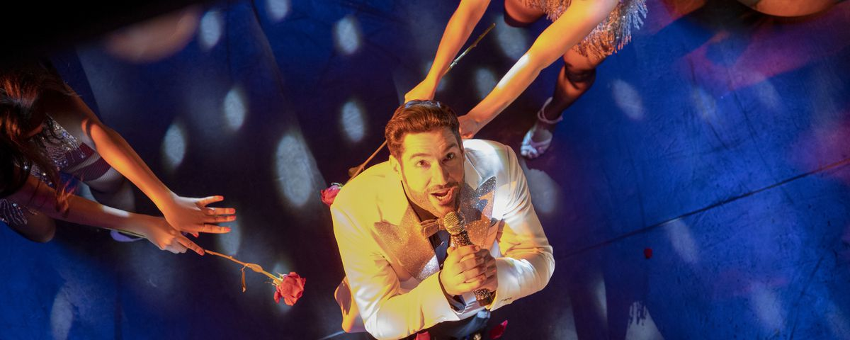 Tom Ellis as Lucifer, seen from above as dancers swirl around him in season 6 of Lucifer