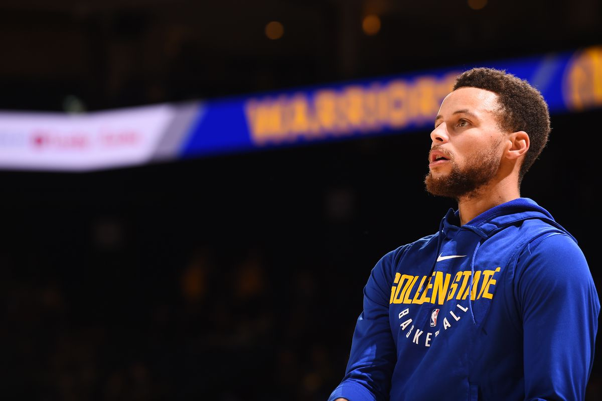 Steph Curry in a purple Golden State hoodie
