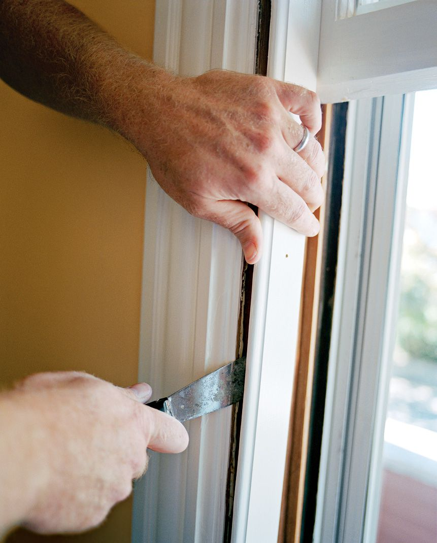 Person prying off the stop inside a double hung window.