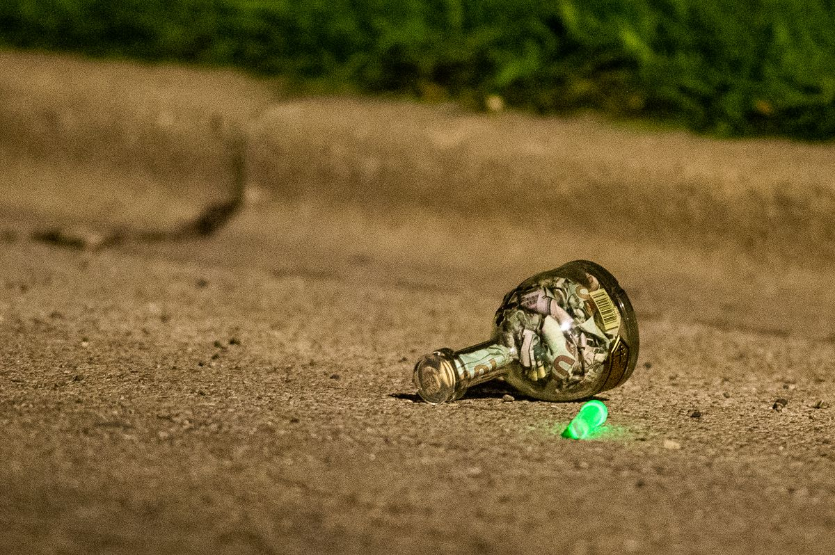 A liquor bottle full of money was left at the scene where a person was shot and killed, Monday morning, in the 200 block of North Long, in the South Austin neighborhood.   Tyler LaRiviere/Sun-Times