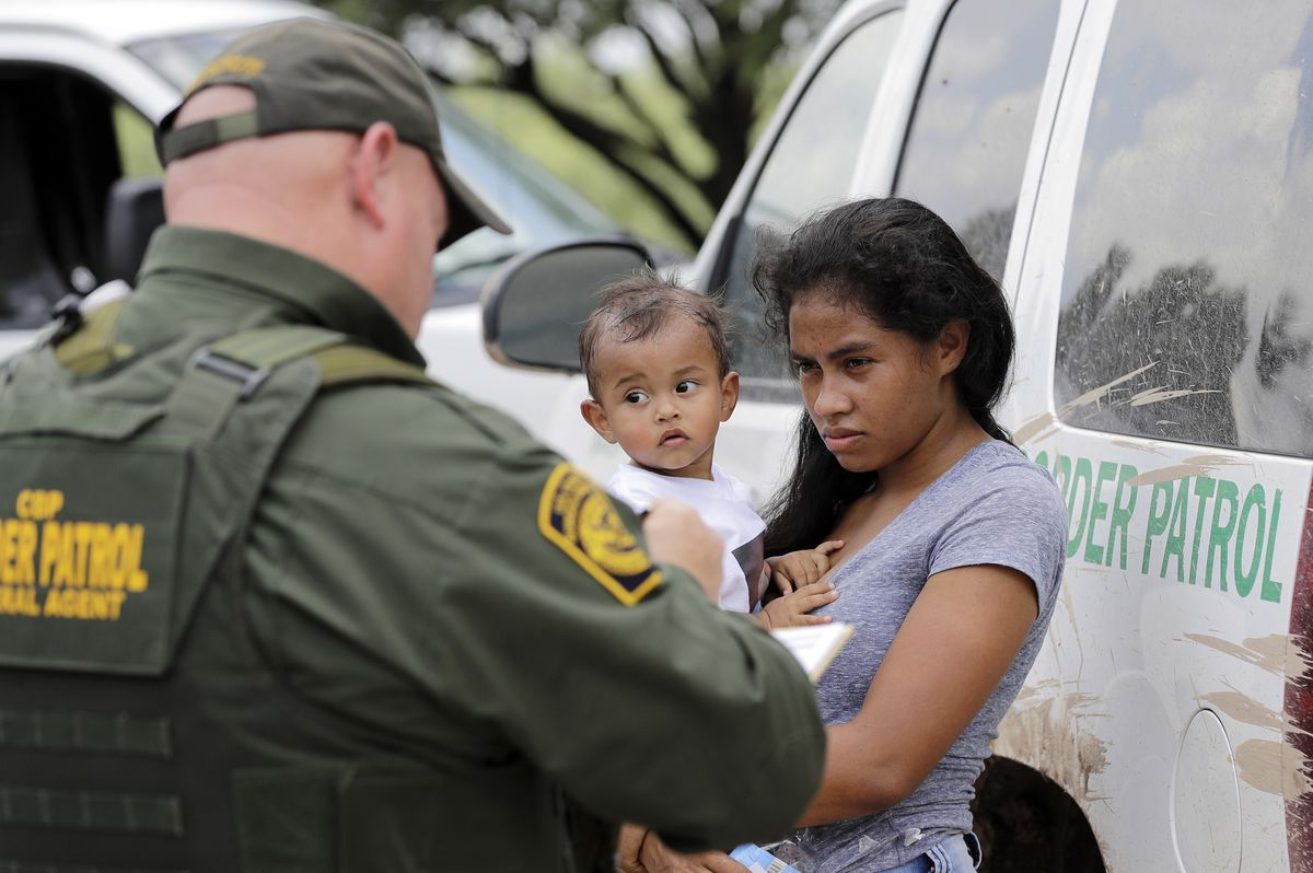 A mother migrating from Honduras holds her 1-year-old child as surrendering to U.S. Border Patrol agents after illegally crossing the border on June 25, 2018, near McAllen, Texas. | AP Photo/David J. Phillip