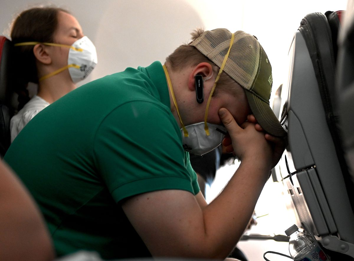 A man with his head in his hands on an airplane.
