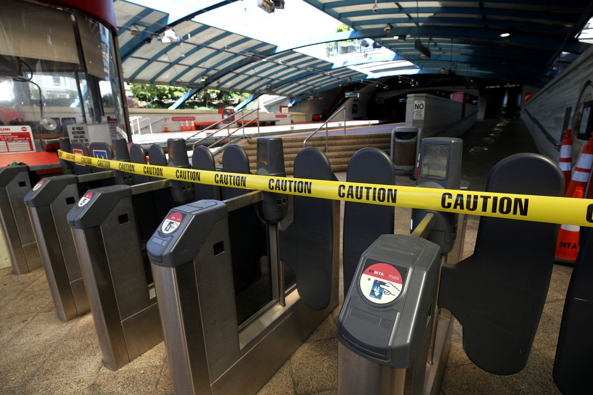 Gates at the San Francisco MUNI Metro West Portal station are blocked with caution tape.