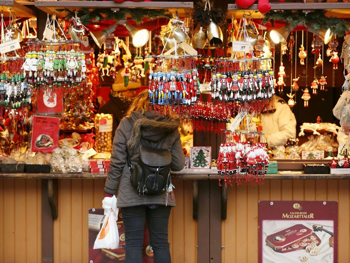 A holiday market vendor stall with ornaments, wooden santas, and Christmas decor.