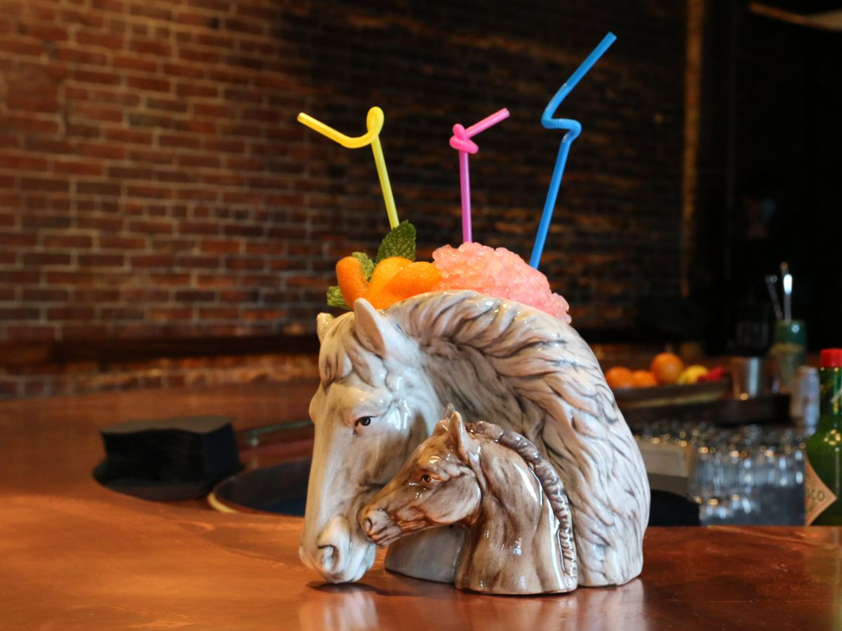 Specialty bar glassware: a horse head with a pony head cozying up to it. A frozen cocktail and neon bendy straws are coming up out of the top. The glassware sits on a curved wooden bar with a brick wall in the background.