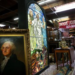 A portrait of George Washington by contemporary artist James Kirkland and a Tiffany stained glass window, circa 1921, sit with other items at Euro Treasures Antiques in Salt Lake City on Thursday, June 8, 2017.