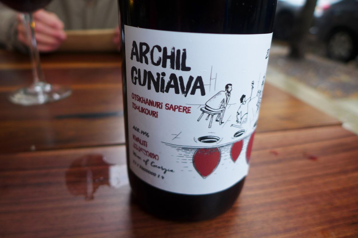 A bottle of red wine with a cartoonish label.