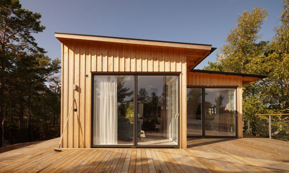 Timber house with flat roof and large glass windows on a wooden deck.