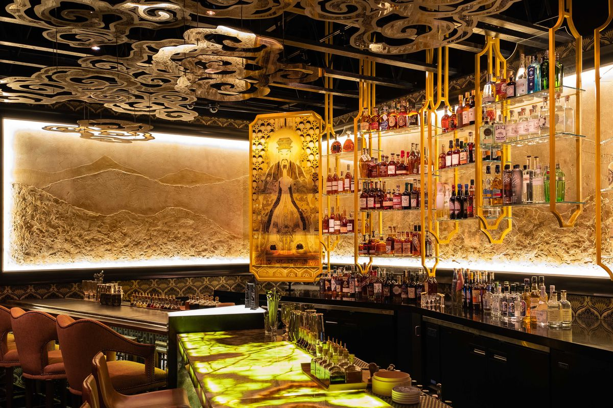 The bar at Realm of the 52 Remedies has gold accents and hanging racks with bottles of liquor.