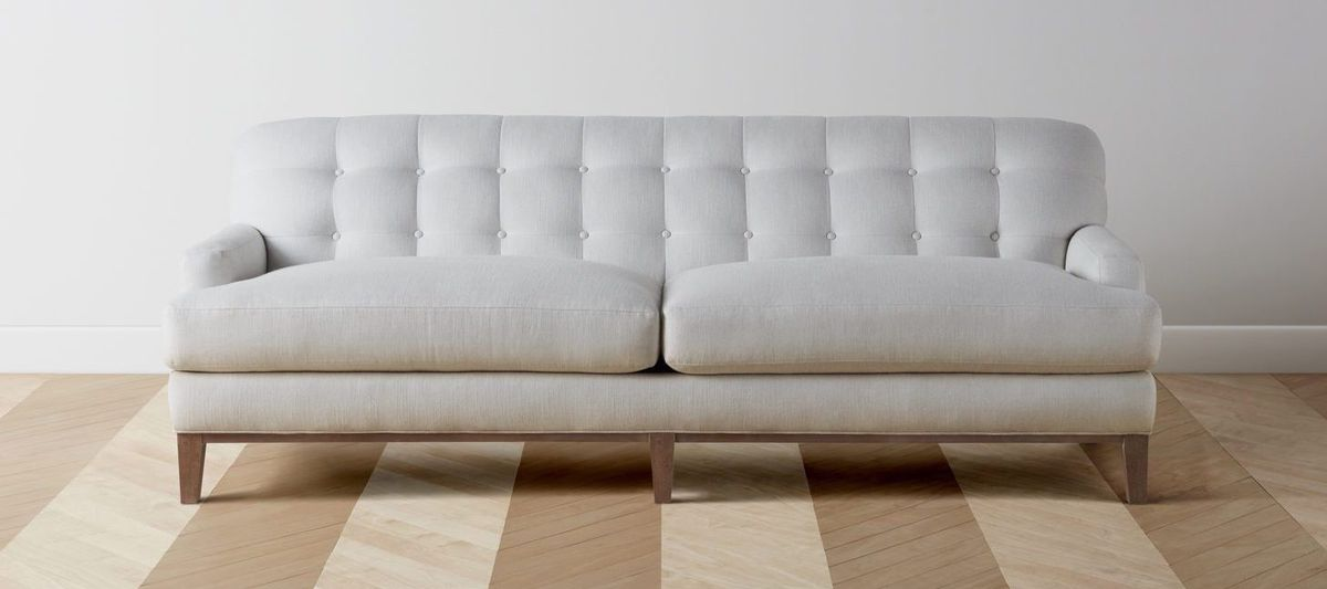 Gray two-seat tufted sofa.