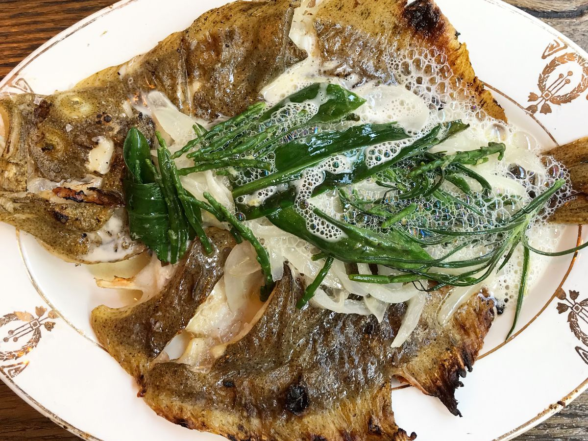 As seen from above, a whole roasted fish on a decorative china plate with a foaming, bubbly sauce and large handful of herbal garnish on top.