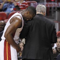 Miami Heat's Dwyane Wade, left, grimaces after hurting his finger as he leans on athletic trainer Jay Sabol in the first half of an NBA basketball game against the Washington Wizards in Miami, Saturday, April 21, 2012.