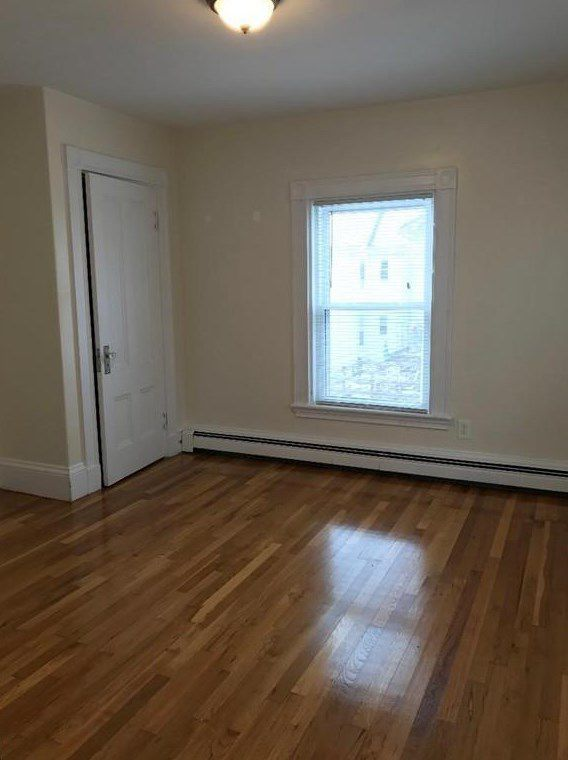 An empty bedroom with a window and a closed closet door.