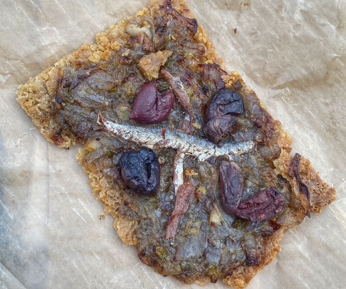 A piece of pissaladière, with caramelised onions, anchovy, and black olive, on a piece of wax paper