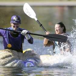 Travis Evans, left, splashes Lydia Martinez as they race in the 2013 Mountain Valley Seed Co. Ginormous Pumpkin Regatta at Sugarhouse Park on Saturday, October 19, 2013.