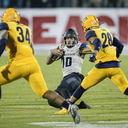 Utah State quarterback Jordan Love (10) slides as Kent State linebackers Kesean Gamble (34) and Mandela Lawrence-Burke (28) defend during the first half of the Frisco Bowl NCAA college football game Friday, Dec. 20, 2019, in Frisco, Texas.