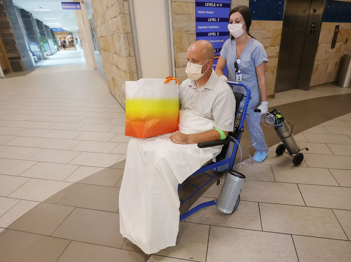Nurse practitioner Aaron Hartle is wheeled out of Utah Valley Hospital by Haley Dunn after being released in Provo on Sunday, July 11, 2021. Hartle was hospitalized with COVID-19 after turning down the vaccine and now wants to urge others to get the shots.