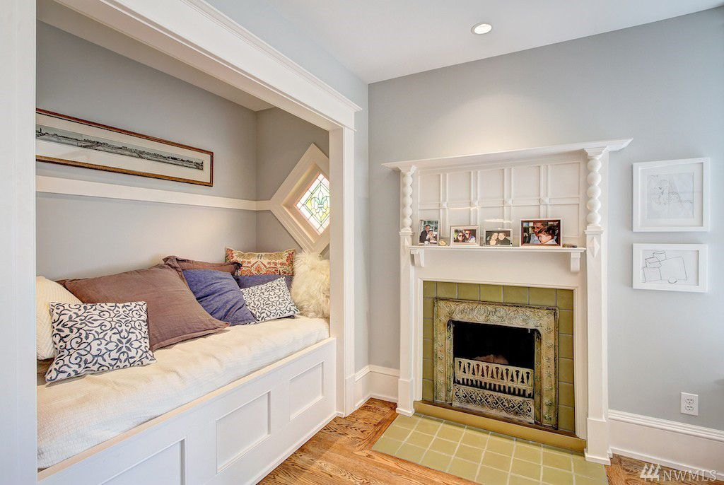 A room with a built-in bench and a small fireplace. A diamond-shaped window sits on the end of the reading nook.