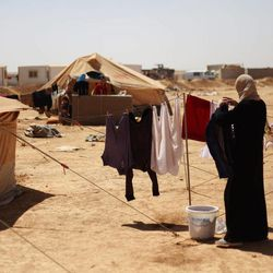 A Syrian refugee woman hangs her families clothes to dry at Zaatari Refugee Camp, in Mafraq, Jordan, Sunday, Sept. 2, 2012.