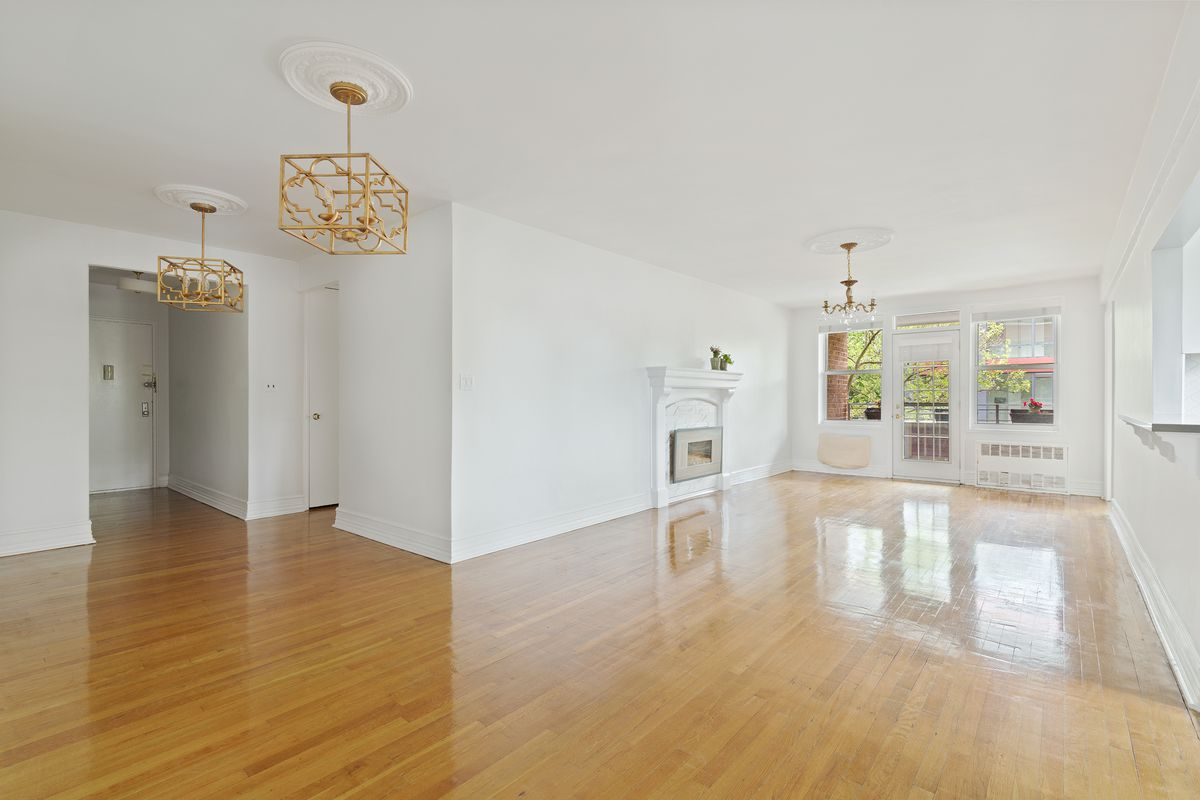 A living area with hardwood floors, several golden light fixtures, a white wall, and an electric fireplace.