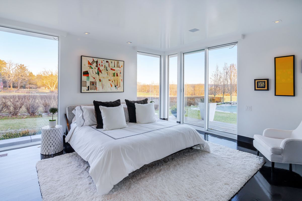 A white bed sits on a white sheepskin rug. A white arm chair faces it and there are large windows on either side of the bed.