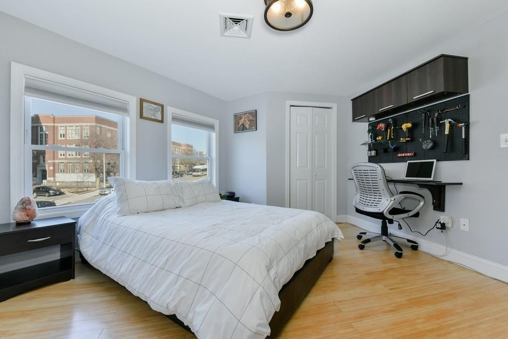 A bedroom with a bed in front of two windows, and the bed's facing a desk with a chair and tools mounted above it.