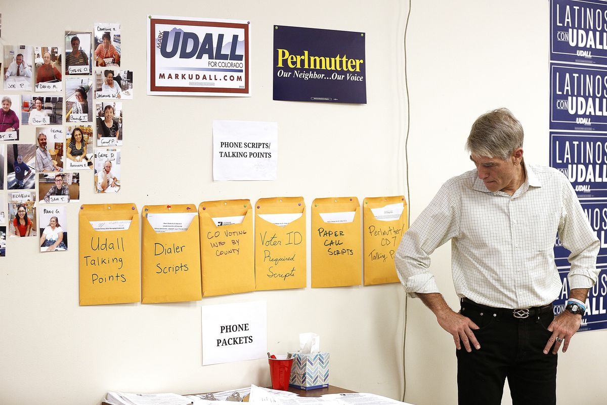 fee19ba75f8a U.S. Senator Mark Udall glances down at phone packet and talking point  materials while waiting to be introduced at a canvass kickoff campaign on  October 25
