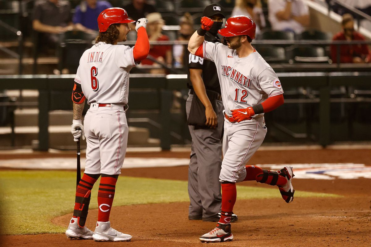 Tyler Naquin #12 of the Cincinnati Reds high fives Jonathan India #6 after hitting a solo home-run against the Arizona Diamondbacks during the fourth inning of the MLB game at Chase Field on April 09, 2021 in Phoenix, Arizona.