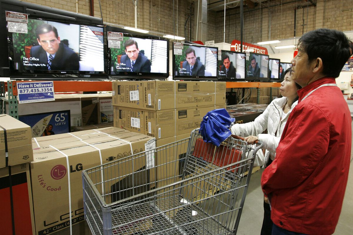 Two people watch The Office on TVs in Costco