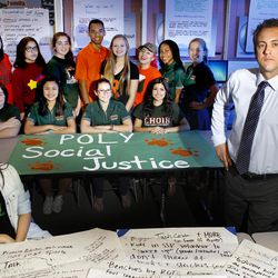 The Poly Social Justice Council, back row, poses with student and editor of the school newspaper, Ashley Gore, and Principal Michael Roe, in their meeting place in the library on Feb. 16,  2016, in the city of Riverside.