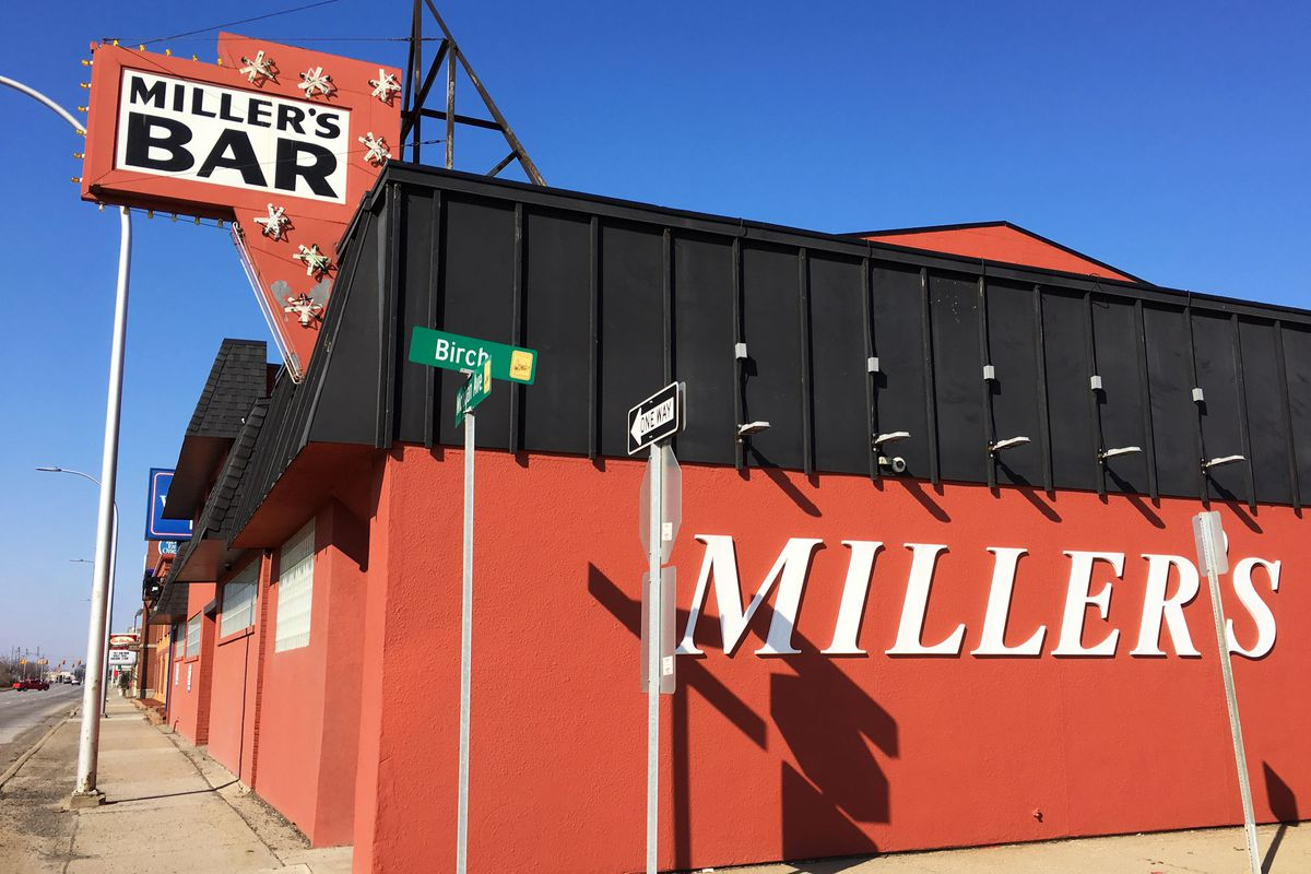 The red, brick exterior of Miller's bar has the word Miller's on the side of the building, and a sign on top that reads Miller's Bar. It's on a corner.