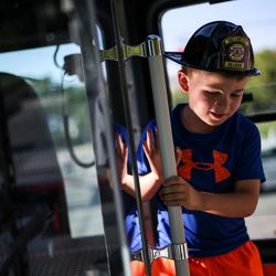 Landon Munns, 7, checks out one of the Salt Lake City Fire Department's two new ladder trucks at Smith's Ballpark in Salt Lake City on Tuesday, June 27, 2017.