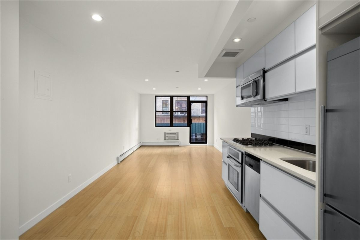 A living area with hardwood floors, white walls, and a kitchen with white cabinetry on the right side.