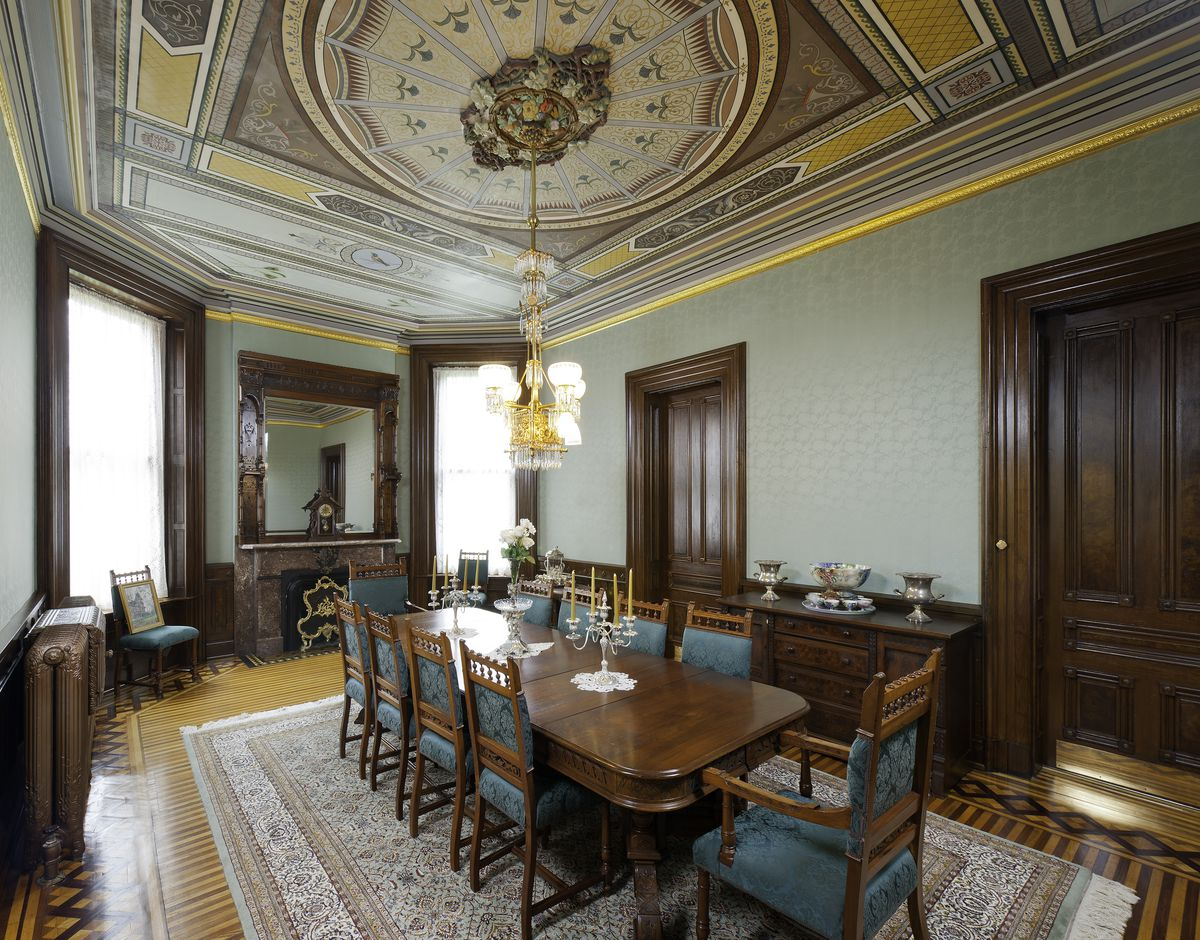 A formal dining room has an elaborate gold printed ceiling, mint walls, and a gold chandelier. There is a 10-person wood and teal dining set.